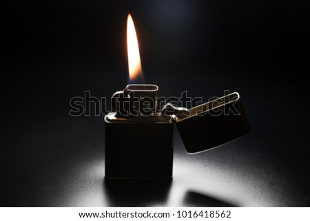 Zippo Lighter With Yellow Flame Isolated On Black Background