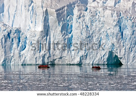 Zodiac tour near enourmous glacier in Paradise Bay, Antarctica - stock photo