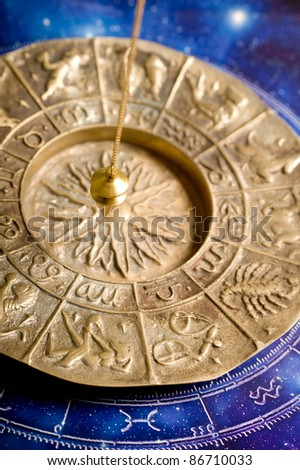zodiac with a pendulum over astrological background - stock photo