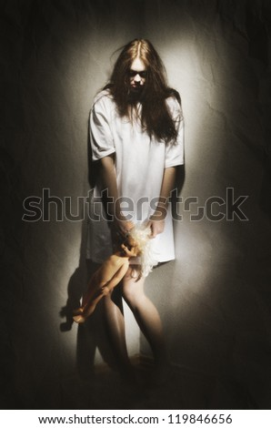 Zombie girl holding plastic doll (ancient version) - stock photo