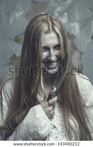 zombie girl over cracked wall background with knife - stock photo