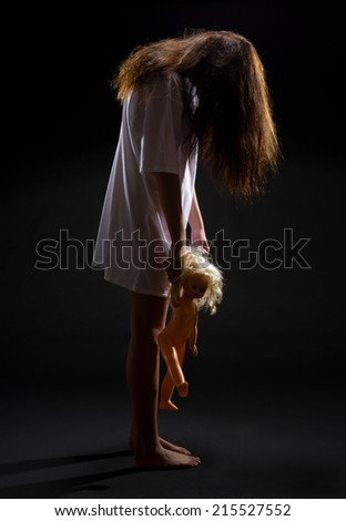 Zombie girl with doll on black - stock photo