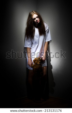Zombie girl with teddy bear on black - stock photo