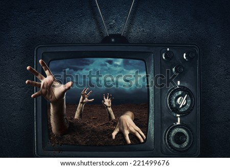 Zombie hand coming out of TV - stock photo
