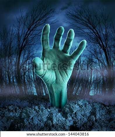 Zombie hand rising out of the ground in a spooky dark forest with creepy trees and fog as a symbol of Halloween imagination with a dangerous monster coming back from the dead. - stock photo