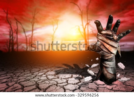 Zombie hand through Soil cracked in Magic land and blurred tree die background.Halloween theme - stock photo
