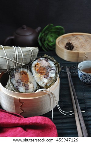 Zongzi in bamboo steam container with chopstick on black background - stock photo