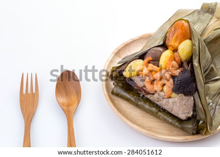 Zongzi or sticky rice dumpling and spoon and fork on white background - stock photo