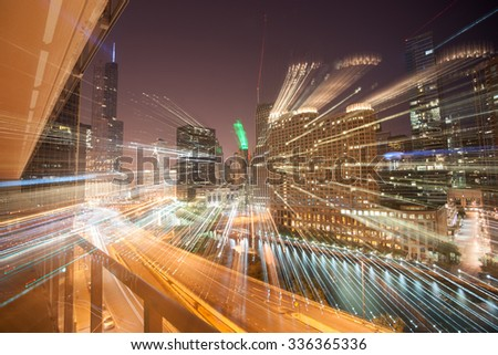 Zoom light streams from city buildings at night accentuate the the density and skyline of architecture and cityscapes of  Chicago, Illinois, USA. - stock photo