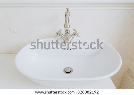 Zoom of sink with old style basin tap - stock photo