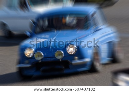 Zooming on a blue french car going fast. Vehicle headlights are on.
