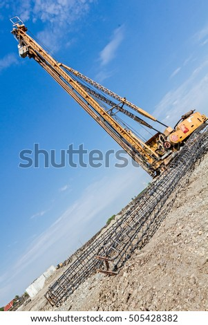 Zrenjanin, Vojvodina, Serbia - April 24, 2015: Basic profile made of bended and tied reinforcing rod in a round shape. Pile driving machine with big auger, equipment for drilling into the ground.