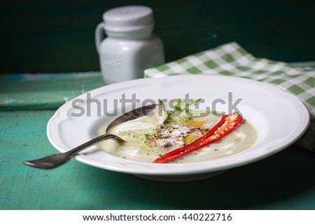 Zucchini cream soup with red pepper, cream, spices and balsamic cream on a wooden background, closeup   - stock photo