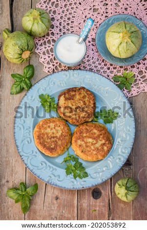 Zucchini fritters on the blue plate with yogurt sauce