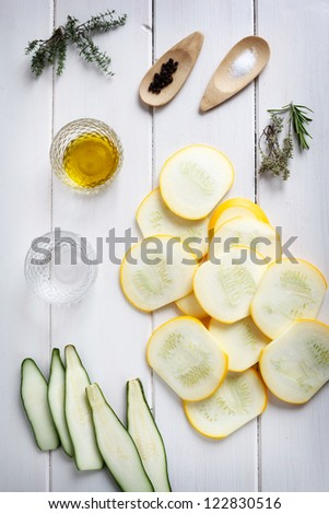 Zucchini slices, pepper, salt and oil for zucchini antipasti. - stock photo