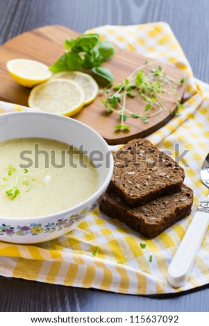Zucchini soup with barley grains and lemon in a bowl