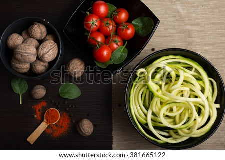 Zucchini spirals in black bowl with a bunch of walnuts and cherry tomatoes - stock photo