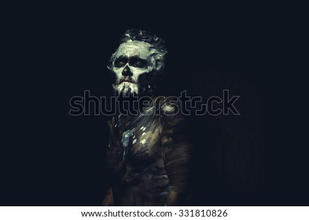 Zulu, wild man with white painted face and full body black paint - stock photo