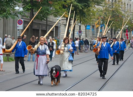 ZURICH - AUGUST 1: Swiss National Day parade on August 1, 2009 in Zurich, Switzerland. Musicians marching with traditional swiss alphorns - stock photo