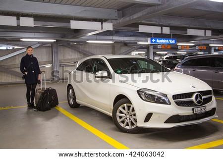 Zurich, Switzerland. March 10, 2016. Beautiful girl standing by the white Mercedes parked in the underground parking. - stock photo
