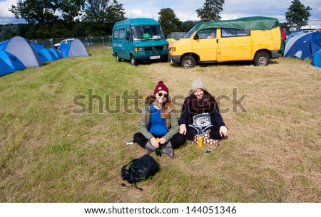 """ZWENTENDORF, AUSTRIA - JUNE 1: Two young girls have rest on the music festival """"Tomorrow"""" near the first austrian atomic plant built in 1976, Zwentendorf Nuclear Power Plant on June 1, 2013 in Austria - stock photo"""