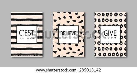 """A set of hand drawn brushstrokes designs. Black paint patterns on pastel pink background with text in black and white. """"C'est la Vie"""" (French for """"That's Life""""), """"Believe in Yourself"""", """"Give More"""". - stock vector"""
