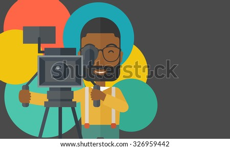 An African American cameraman with beard and glasses looking through movie camera on a tripod vector flat design illustration. Horizontal layout with a text space. - stock vector