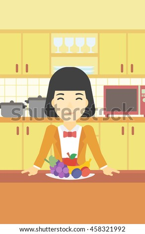 An asian woman standing in front of table full of fresh fruits in the kitchen. Woman with plate full of fruits. Healthy food concept. Vector flat design illustration. Vertical layout. - stock vector