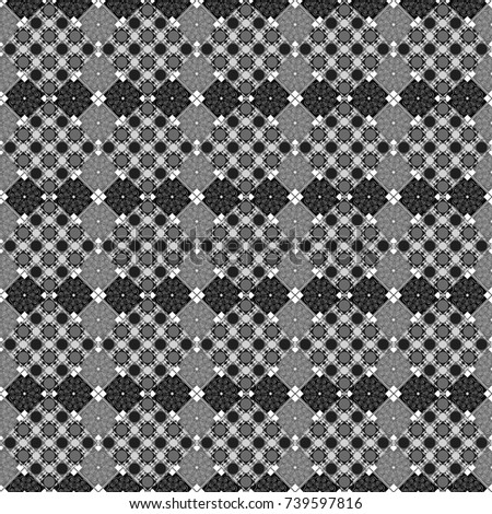 Black, white and gray ethnic geometric motif seamless pattern in black, white and gray on abstract background.