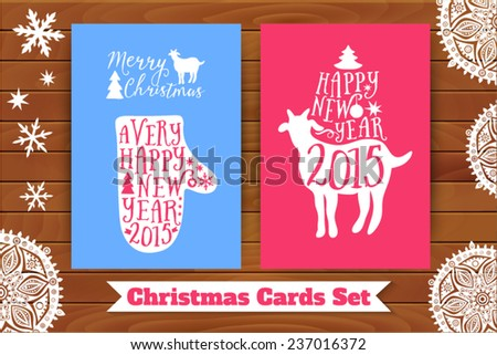 Christmas card set. Goat and mitten with lettering elements, on table top. Decorated with paper snowflakes - stock vector