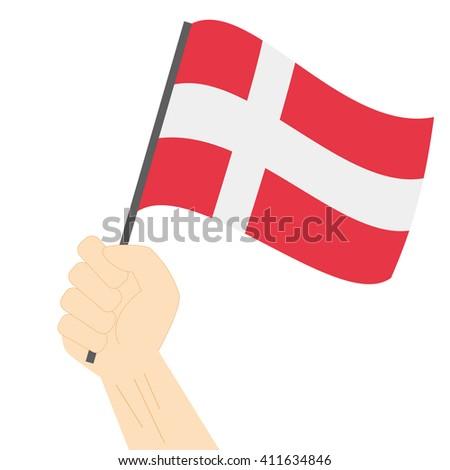 Hand holding and raising the national flag of Denmark - stock vector