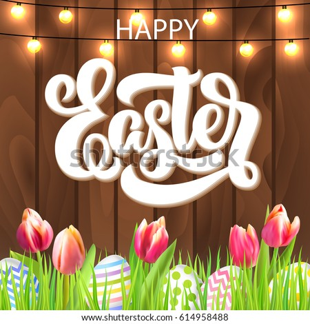 Happy Easter Lettering With Eggs Garland And Tulip Flowers In Grass On Rustic Wooden Background