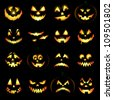 Jack o lantern pumpkin faces glowing on black background - stock photo