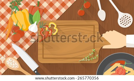 Kitchen wooden worktop with cook's hand holding a chopping board, kitchen tools and vegetables all around, top view - stock vector