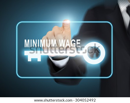 male hand pressing minimum wage key button over blue abstract background - stock vector