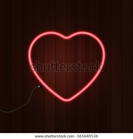 Neon glowing heart on the wooden background
