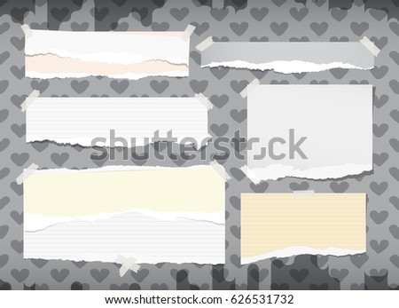 Ripped white and yellow notebook, copybook, note paper strips stuck with sticky tape on grey pattern created of heart shapes