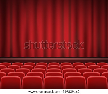 Rows of red cinema or theater seats in front of show stage