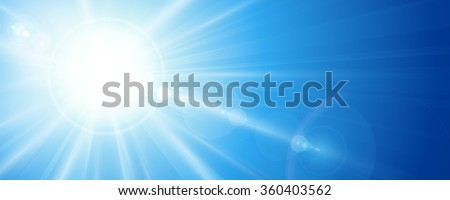 Sun rays and lens flare in a bright blue sky in horizontal, panorama format. Space for your text.