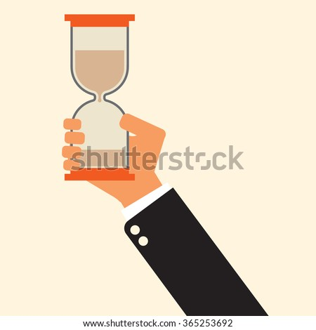 time is running out: businessman holding hourglass