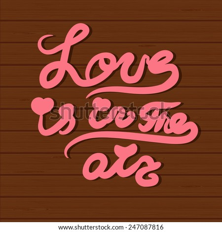 "Vector card with hand lettering  text ""Love is in the air"" and cartoon flowers  on wood background. Valentine`s day, mother`s day, wedding or birthday card design. - stock vector"