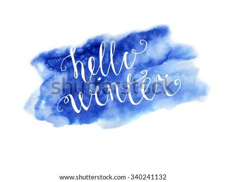 Vector hand written inscription Hello winter. Bright blue hand drawn watercolor texture and white hand written words. Calligraphic phrase. - stock vector
