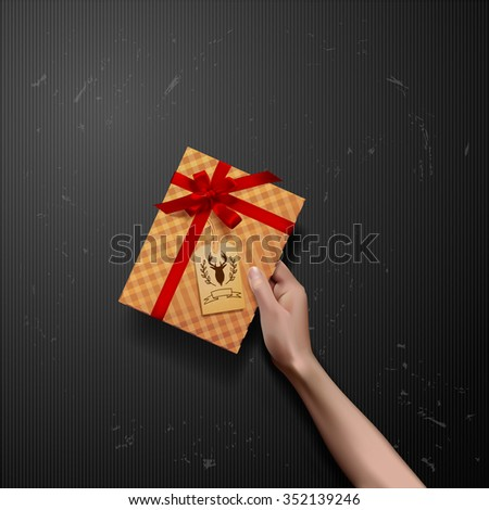 Vector hands holding gift box with red ribbon bow with deer label. gift box in hand - stock vector