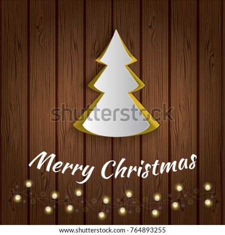 cutout paper christmas tree on wooden background with lights