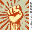 Vector illustration of clenched fist held high in protest on the red grunge urban background - stock photo