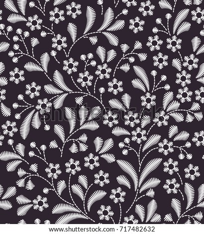 Vector seamless pattern. Floral background in vintage style. Decorative embroidery flowers. Ornament for textiles on black background. Small white flowers. The elegant the template for fashion prints.