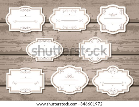 Vector set of labels and tags with frames and decorative elements. On wooden background. - stock vector