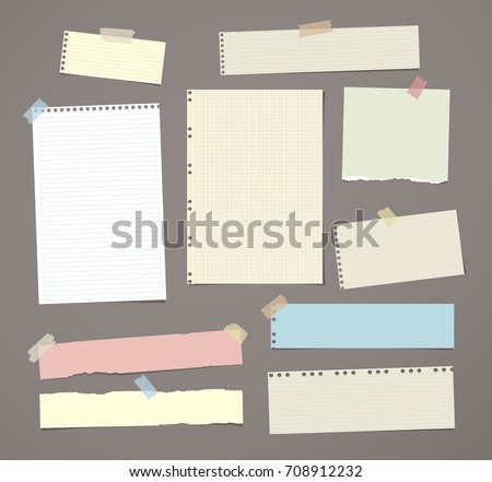 White and colorful striped note paper, copybook, notebook sheet stuck with adhesive tape on dark brown background.