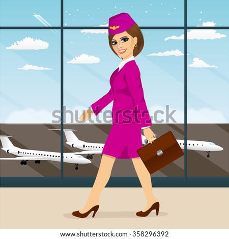 young attractive stewardess with briefcase in pink uniform walking through airport terminal